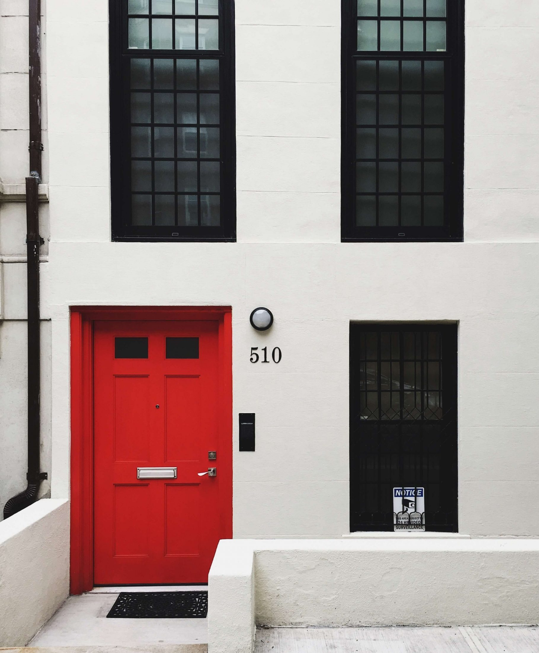 Black windows on a white home with a red door