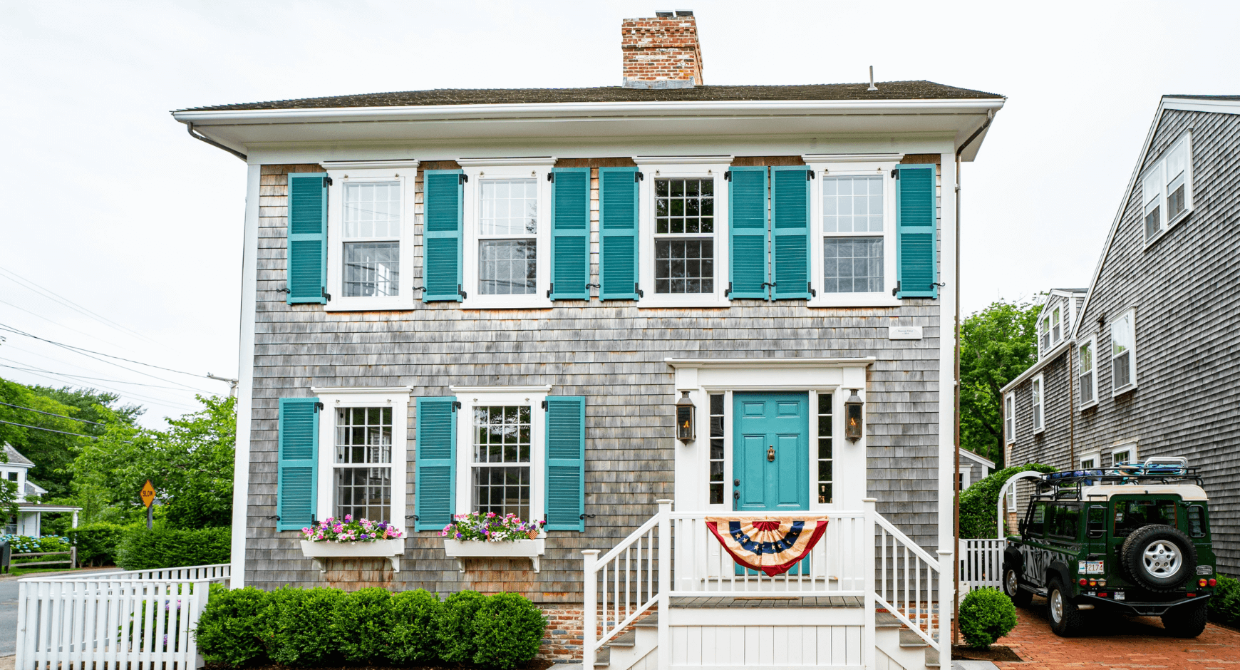 Image of a home with farmhouse window trim and blue shutters