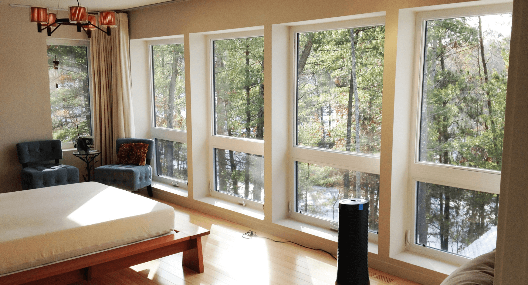 Image of a home with large windows looking out into the woods