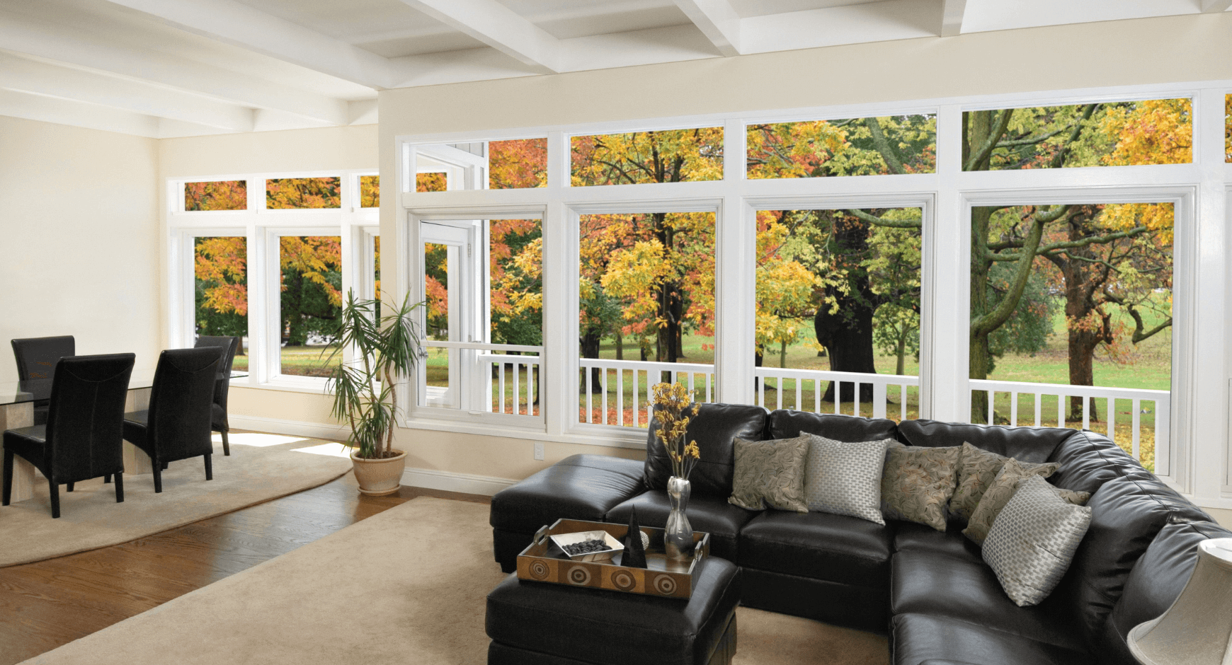 Image of a comfortable home with large windows looking out into the fall woods