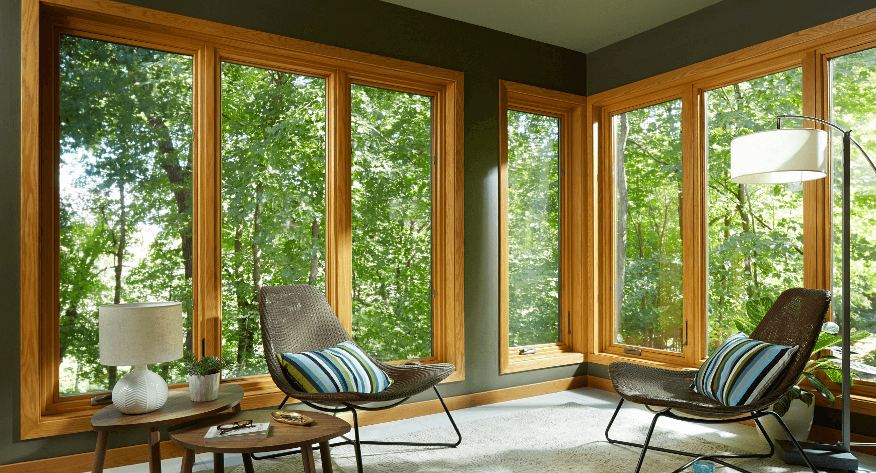 Image of an energy efficient home with large picture windows looking out into the woods