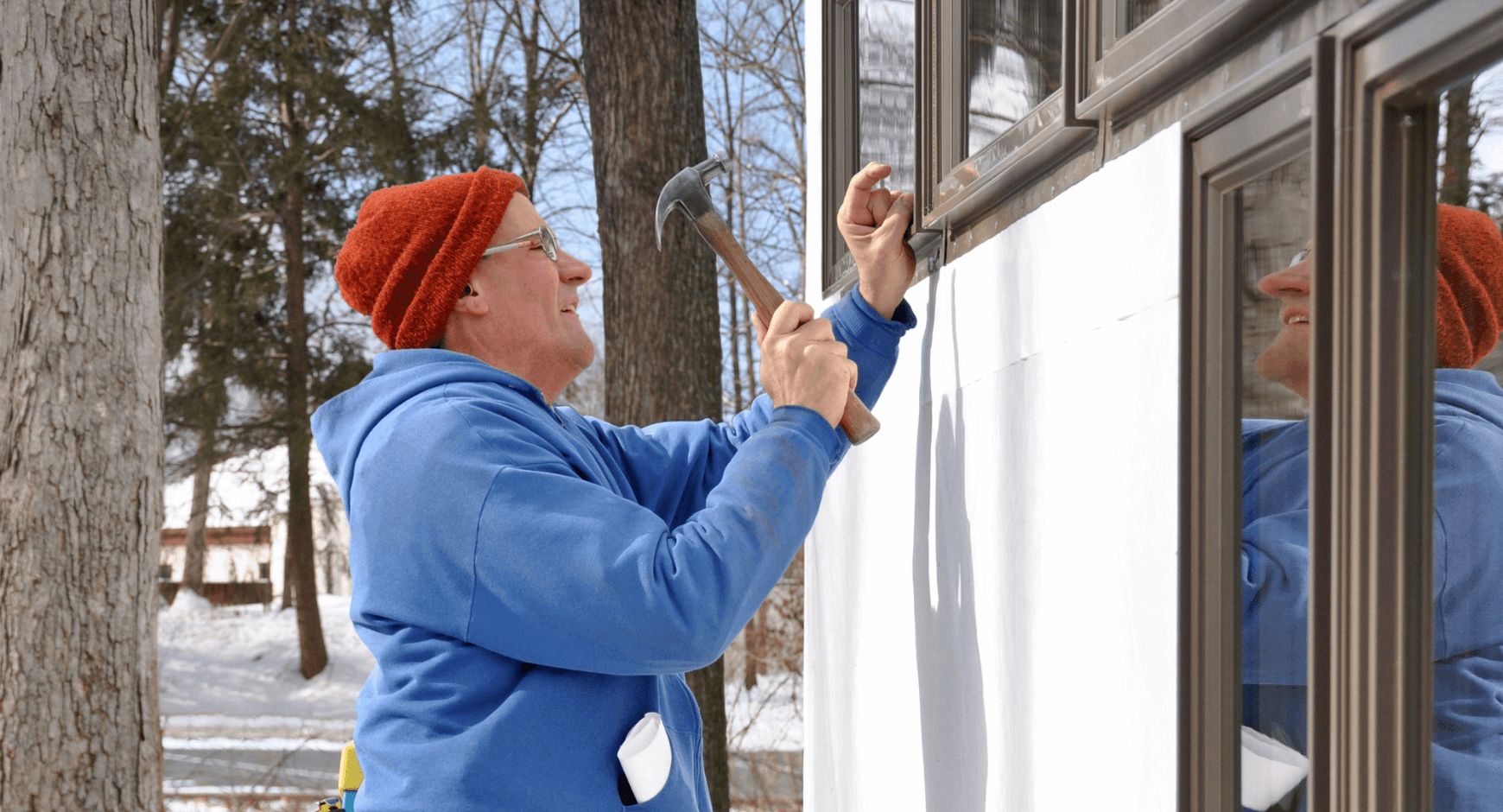 Image of a man replacing windows during the winter in the snow