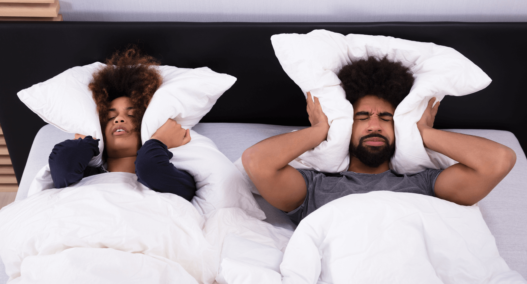 Image of a couple holding pillows over their ears